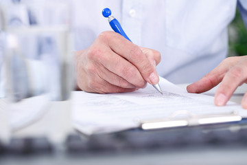 Man's  hand with pen signing document