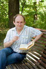 Mature pretty man reading book, outdoor.