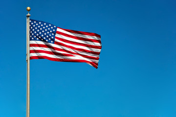 US American flag waving in the wind with beautiful blue sky in b