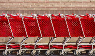 Line of Red Shopping Carts by Brick Wall