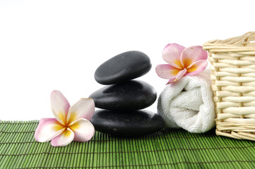 Zen stones and roller towel and wicker basket with frangipani