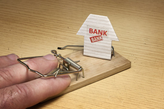 Hand of man caught in mousetrap set by the bank