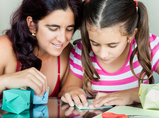 Mother and daughter making paper models at home