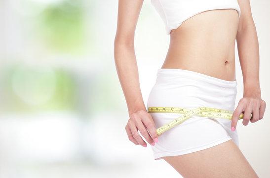 Woman measuring perfect shape of beautiful hips
