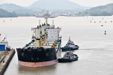 Tugboats pushing ship in the Panama Channel