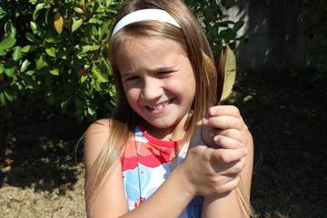bambina che tiene delle foglie