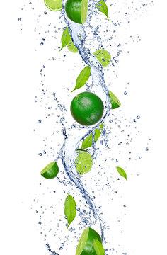 Fresh limes falling in water splash