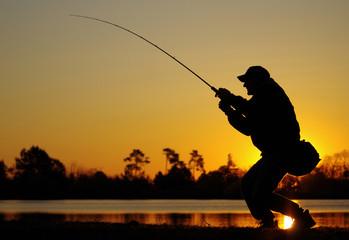 Pêcheur combattant un poisson au soleil couchant