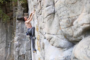 Rock climber struggling to make the next movement