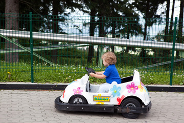 Little blond toddler driving car in amusement park