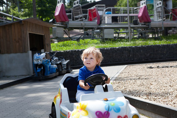Little baby boy driving car in amusement park
