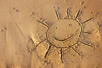 Sun drawn in the sand/Sea background with a sand
