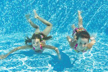 Wall Mural - Happy smiling underwater children in swimming pool, kids sport