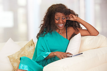 African lady with tablet-pc sitting on the sofa
