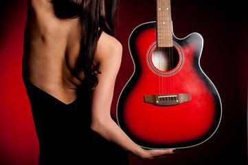 Carmen beautiful woman with guitar on dark background