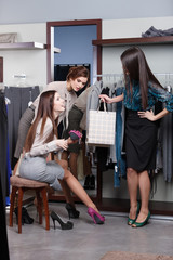 Woman consults with friends concerning new fuchsia shoes