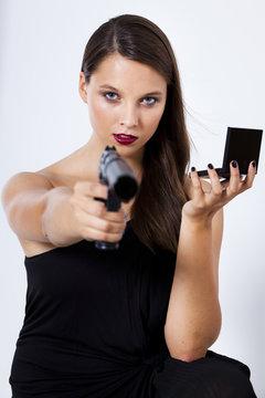 weiblicher agent mit pistole im anschlag und schminkspiegel