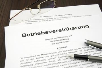 Betriebsvereinbarung mit Brille und Füller