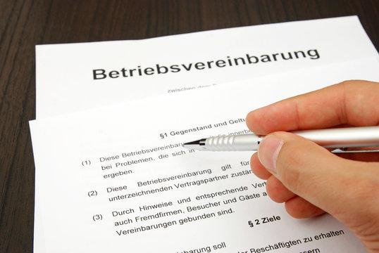 Betriebsvereinbarung mit Hand und Kugelschreiber