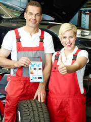 Apprentice and mechanic showing thumb up for tyre labeling