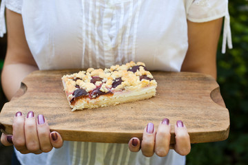 Fresh baked plum cake on cutting board with woman hands
