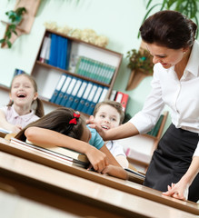 Teacher wakes a sleeping at the desk schoolgirl up