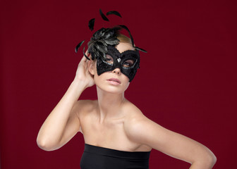 Beautiful woman with black masquerade mask with feathers
