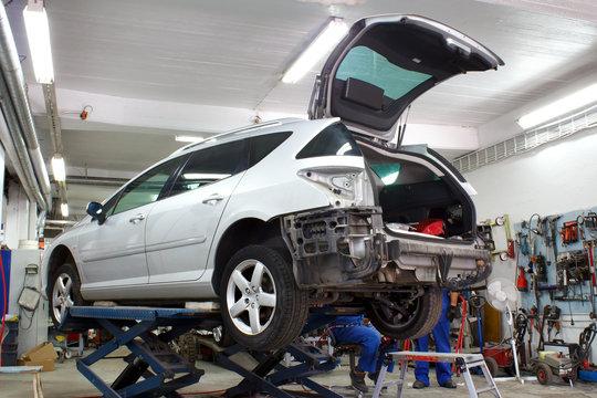 Car is lifted in car body repair service