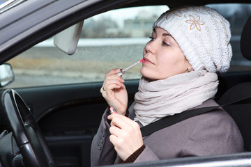 Caucasian female does make up in car, looking at mirror