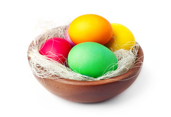 Colorful Easter eggs in wooden bowl, isolated on white