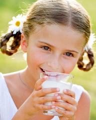Healthy kid - lovely girl drinking fresh milk outdoors