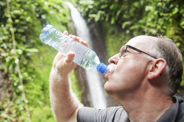 Adult man drinking a cold bottle of water