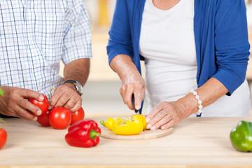 älteres paar schneidet gemüse in der küche