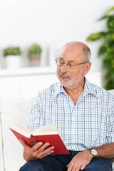 älterer mann liest ein buch auf dem sofa