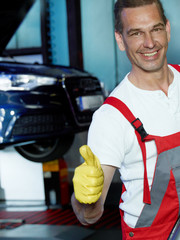 Master mechanic in a garage shows ok for good service