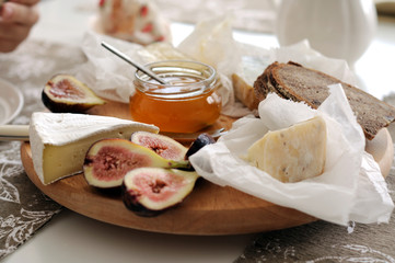 Cheese platter with French cheeses, honey and figs
