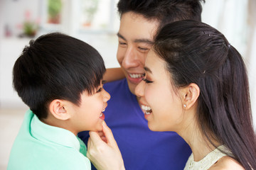 Head And Shoulders Portrait Of Chinese Family Together At Home