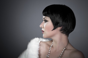 gourgeos female brunette flapper profile wearing pearls and fur