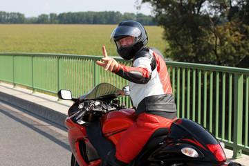 Wall Mural - Mann auf Motorrad zeigt Finger
