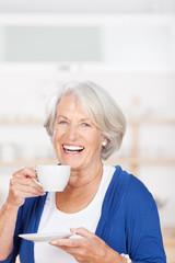 glückliche ältere frau trinkt kaffee