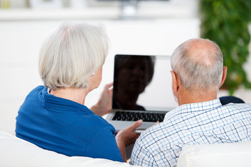 älteres ehepaar schaut auf den laptop