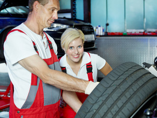 Female apprentice for mechanic learning to fit a summer tyre