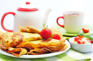 Pancakes with fresh strawberry and cup of tea