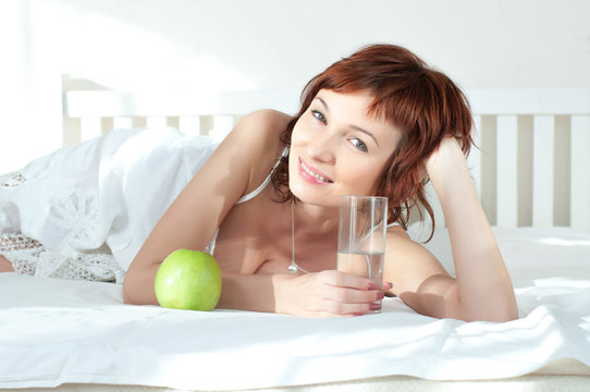 attractive young woman with an green apple and glass of water