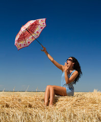 girl in the summer in the field with a departing umbrella