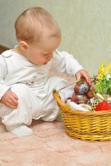 The kid near a basket with colored eggs sits