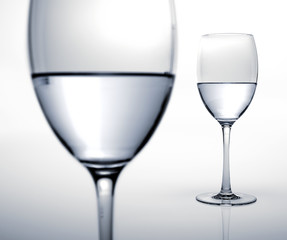 Two glasses half filled of water.