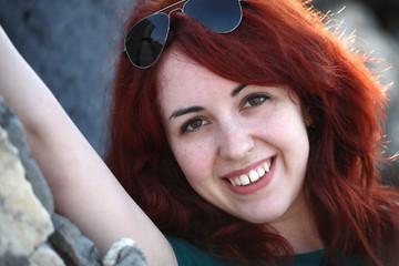 Ragazza con capelli rossi e occhiali da sole