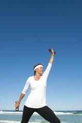 Active senior woman ocean background