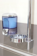 Faucet with soap dispenser in bathroom.